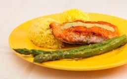 Faixa vermelha do bife da truta com arroz e aspargo em uma placa amarela foto de stock royalty free