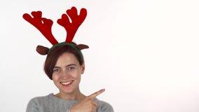 Faixa vestindo dos chifres da rena da jovem mulher que aponta no espaço da cópia filme