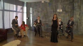 A faixa viva com cantor fêmea executa na festa de anos pequena A jovem mulher 'sexy' bonita canta a música com músicos dentro video estoque