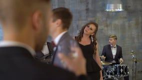A faixa viva com cantor fêmea executa na festa privada pequena A jovem mulher 'sexy' bonita canta a música com os músicos na barr video estoque