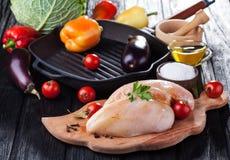 Faixas cruas da galinha na placa de corte de madeira, com vegetais Imagens de Stock