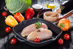 Faixas cruas da galinha na placa de corte de madeira, com vegetais Imagem de Stock