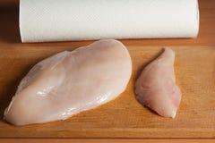 Faixas cruas da galinha na placa de corte de madeira, vista superior Imagem de Stock