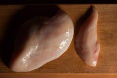 Faixas cruas da galinha na placa de corte de madeira, vista superior Sombras profundas Fotos de Stock Royalty Free