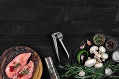 Faixas cruas do peito de frango na placa de corte de madeira com ervas e especiarias Vista superior com espaço da cópia Imagens de Stock