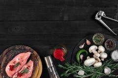 Faixas cruas do peito de frango na placa de corte de madeira com ervas e especiarias Vista superior com espaço da cópia Foto de Stock