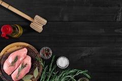 Faixas cruas do peito de frango na placa de corte de madeira com ervas e especiarias Vista superior com espaço da cópia Fotos de Stock
