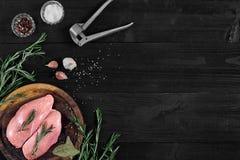 Faixas cruas do peito de frango na placa de corte de madeira com ervas e especiarias Vista superior com espaço da cópia Fotografia de Stock