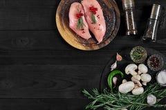 Faixas cruas do peito de frango na placa de corte de madeira com ervas e especiarias Vista superior com espaço da cópia Fotografia de Stock Royalty Free