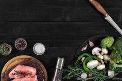 Faixas cruas do peito de frango na placa de corte de madeira com ervas e especiarias Vista superior com espaço da cópia Foto de Stock Royalty Free