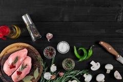 Faixas cruas do peito de frango na placa de corte de madeira com ervas, especiarias, cogumelos e pimentas de pimentão Vista super Imagem de Stock