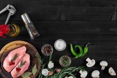 Faixas cruas do peito de frango na placa de corte de madeira com ervas, especiarias, cogumelos e pimentas de pimentão Vista super Foto de Stock
