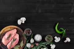 Faixas cruas do peito de frango na placa de corte de madeira com ervas, especiarias, cogumelos e pimentas de pimentão Vista super Imagens de Stock