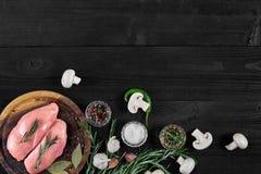 Faixas cruas do peito de frango na placa de corte de madeira com ervas, especiarias, cogumelos e pimentas de pimentão Vista super Imagem de Stock Royalty Free