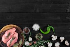 Faixas cruas do peito de frango na placa de corte de madeira com ervas, especiarias, cogumelos e pimentas de pimentão Vista super Fotos de Stock Royalty Free