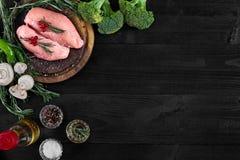Faixas cruas do peito de frango na placa de corte de madeira com ervas, especiarias e vegetais Vista superior com espaço da cópia Imagens de Stock Royalty Free
