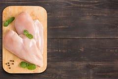 Faixas cruas do peito de frango no fundo de madeira com muito co Fotos de Stock Royalty Free