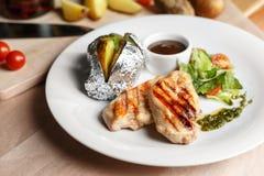 Faixas da galinha, pimenta de pimentão e cereja grelhadas dos tomates batatas cozidas na folha fotos de stock royalty free