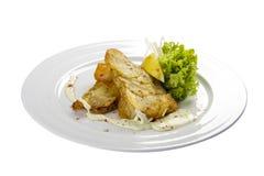 Faixas de bacalhau com lim?o e salada fotografia de stock royalty free