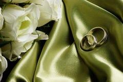 Faixas de casamento no cetim verde Fotos de Stock Royalty Free