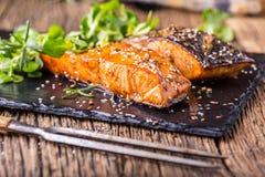 Faixas Salmon cruas Salmões grelhados, decorationon da erva das sementes de sésamo na bandeja do vintage ou placa preta da ardósi Foto de Stock