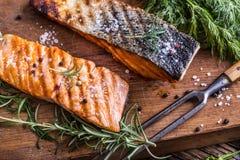 Faixas Salmon cruas Salmões grelhados, decorationon da erva das sementes de sésamo na bandeja do vintage ou placa preta da ardósi Fotografia de Stock Royalty Free