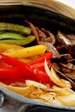 Fajitas. Cast iron skillet full of fajita ingredients; tortillas in background Royalty Free Stock Photos
