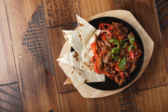 Fajitas with beef. And bell pepper in a pan. Wooden background Royalty Free Stock Photography