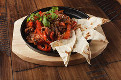 Fajitas with beef. And bell pepper in a pan. Wooden background Royalty Free Stock Image