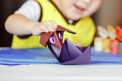 Fake battle, an origami figure Godzilla attacks a. Paper battle, an origami figure Godzilla attacks a paper boat, children's games. The development of stock image