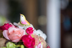A fake bird and Colorful rose flower in pot Royalty Free Stock Image