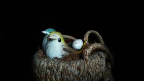 Fake birds sitting with an egg sitting in an artificial nest royalty free stock photography