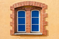 Fake blue windows. Twin windows with bricks underneath one arch, with blue glass panes in orange wall. Fake blue windows Royalty Free Stock Photography