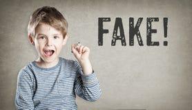 Fake! Boy on grunge background writing Stock Photography