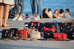 Fake brands sold on Barcelona beach. BARCELONA/SPAIN - 29 OCTOBER 2016: Copies of popular brands of bags sold on the Barceloneta beach Royalty Free Stock Photo