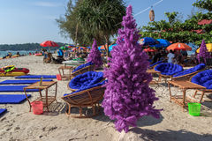 Fake christmas tree on tropical beach with chairs and tables around Royalty Free Stock Photography