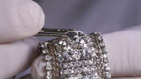Fake Diamond on a Bracelet. Close up Man Hand with White Gloves Putting Diamond on a Bracelet Jewellery Using Tweezers on a White Background stock video