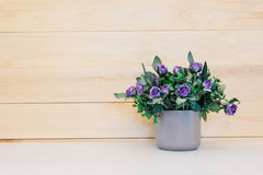 Fake flower in vase on wood background. Royalty Free Stock Photography