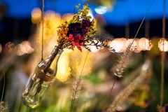 Fake flowers in bottle with bokeh in garden. Colorful fake flowers in decorative bottle hanging in garden with ligh bokeh background at dusk. Wedding outdoor stock images