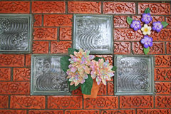 Fake flowers on carving brick wall Royalty Free Stock Images