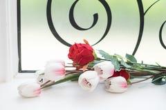 Fake flowers. Fake flowers on glass window Stock Image