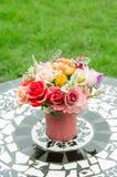 Fake flowers in tin vase Stock Image