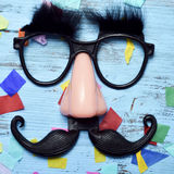 Fake glasses, nose and mustache. Closeup of a pair of fake black glasses with eyebrows, a nose and a mustache forming the face of a man on a blue rustic wooden royalty free stock image