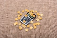 Fake gold coins around the calculator royalty free stock photography
