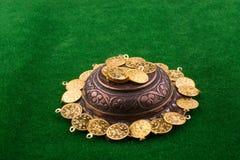 Fake gold coins around a metal plate. Fake gold coins around an old decorative metal plate stock photos