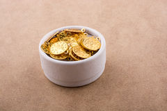 Fake gold coins in a box. Fake gold coins in white box on brown background stock image