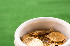 Fake gold coins in a box. Fake gold coins in white box on green grass stock photo