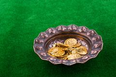 Fake gold coins in a metal  plate. Fake gold coins in an old decorative metal  plate royalty free stock photography