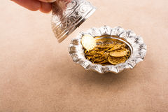 Fake gold coins in a metal plate. Fake gold coins in an old decorative metal plate stock photography