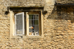 Fake goose at stone window , Lacock. A wooden goose sticks out of a stone window of cottage in historic touristic village of Somerset Stock Photography
